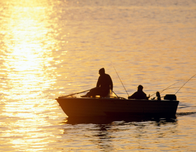 Fisherman on boat at sunrise