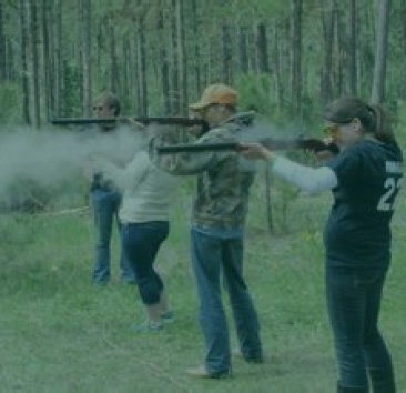 Group of young adults shooting rifles